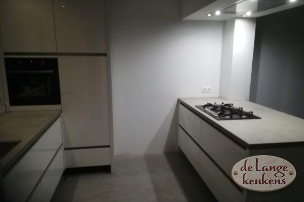 Moderne witte greeploze keuken met betonlook blad