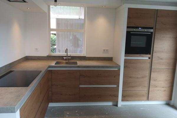 Houten greeploze keuken met witte wanden en betonnen blad