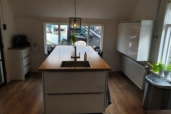 Moderne witte keuken met houten blad