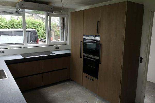 Moderne u-keuken met hoge kastenwand en zwart blad